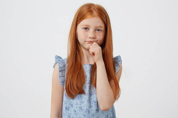 Portrait of little unhappy freckles red-haired girl, sadly looks at the camera, wears in blue dress, stands over white background.