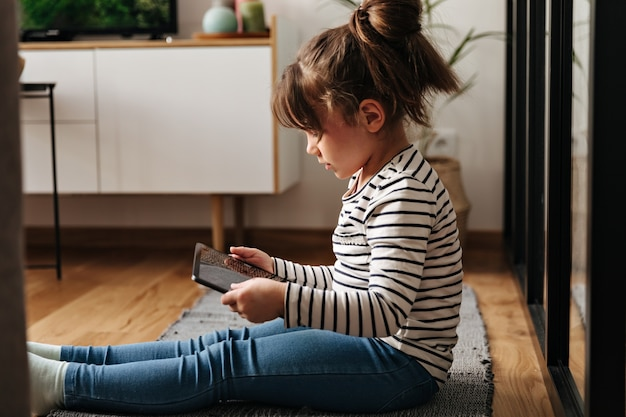 Portrait of little woman in jeans and t-shirt sitting on carpet and holding tablet.