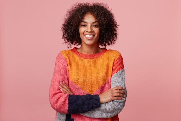 Portrait of lively charismatic attractive african american girl with afro hairstyle looks with excitement, plesantly smiles, stand with arms crossed, wearing colorful sweater, isolated on pink wall