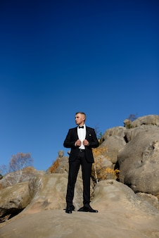 Portrait of a lonely groom on a background of rocks.