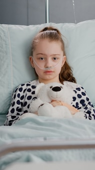Portrait of lonely little child looking into camera holding teedy bear in hands