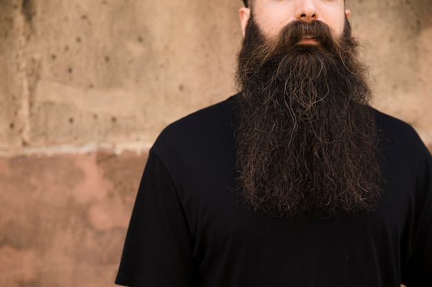 Portrait of a long bearded young man in front of wall