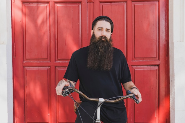 Portrait of a long bearded young man siting on bicycle looking at camera