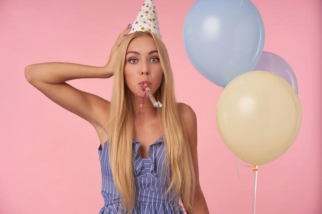 Ritratto di signora bionda dai capelli lunghi in abito estivo blu e berretto di compleanno in posa su sfondo rosa con un mazzo di palloncini di elio, alzando la mano alla testa e guardando la fotocamera con sorpresa