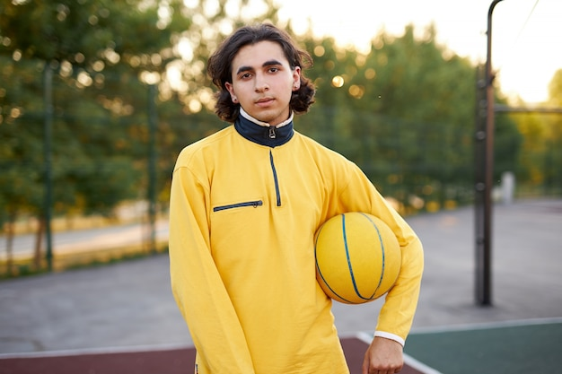 Portrait of long haired caucasian teen boy with ball