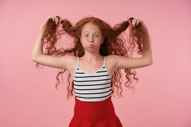 Portrait of long haired curly girl playing with her red hair while standing over pink background, puffing out cheeks and making fun, looking camera with raised eyebrows