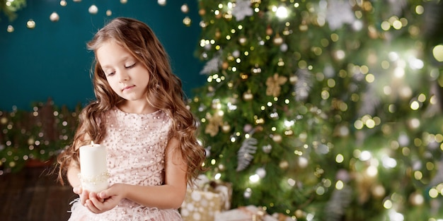 Portrait of long-haired little girl in dress on background of  lights.