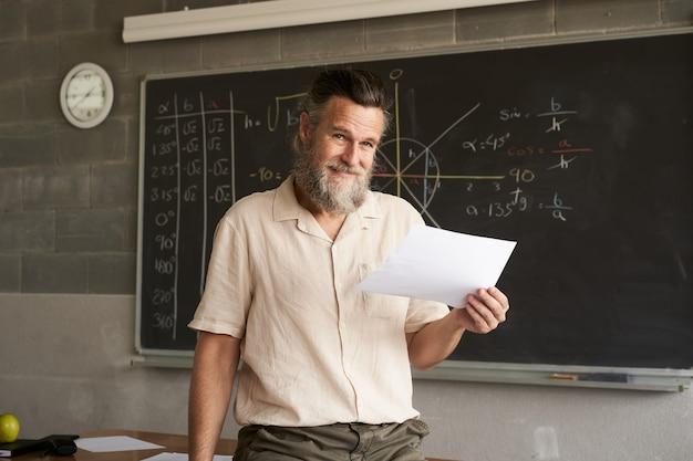 Портрет, глядя в камеру учителя-мужчины в классе, в руке он держит экзамены