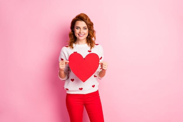 Портрет симпатичной довольно очаровательной веселой девушки в белом пуловере, держащей в руках большое сердце