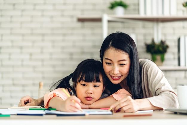 Портрет любви азиатской семьи, матери и маленькой азиатской девочки, которая учится и пишет в книге с карандашом, делая домашнее задание дома