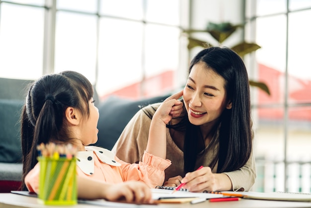 Portrait love asian family mother and little asian girl learning and writing in book with pencil making homework at home