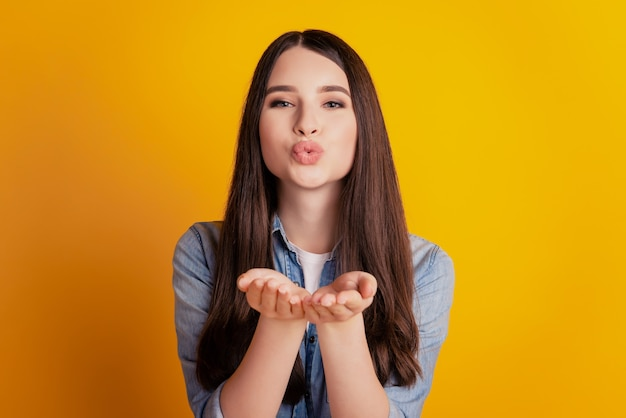 Portrait of a lovely adorable girlfriend sending air kiss on yellow background
