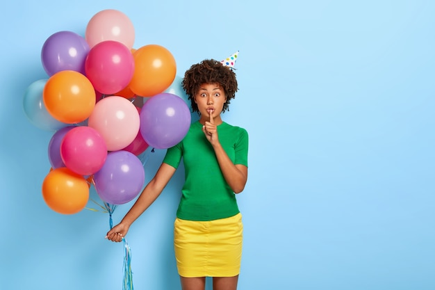 Portrait of lovely afro american woman makes silence gesture, holds bunch of colored balloons, wears green t shirt and yellow skirt, tells secret