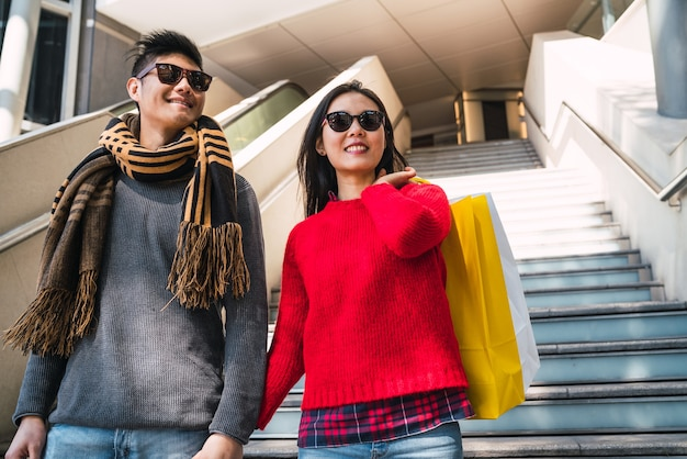 Portrait of lovely asian couple holding colorful shopping bags and enjoying shopping, having fun together in mall.