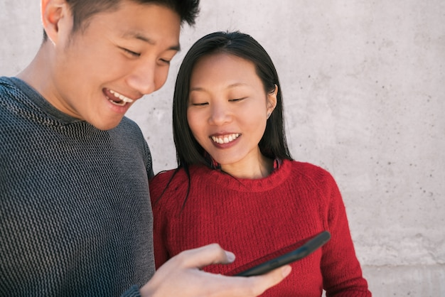 Portrait of lovely asian couple looking at the mobile phone while spending good time together. love and technology concept.