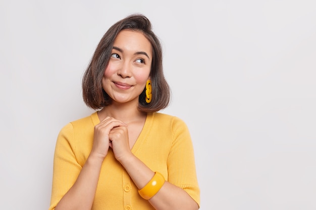 Portrait of lovely asian girl keeps hands together looks away with dreamy expression dreams about something wears casual yellow jumper bracelet on arm isolated over white wall