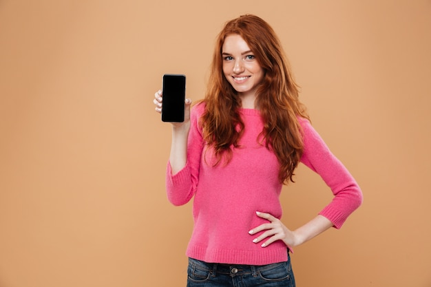 Portrait of a lovely attractive redhead girl showing smartphone