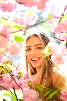 Portrait of lovely blond girl surrounded by pink petals female with big eyes and charming smile on n...