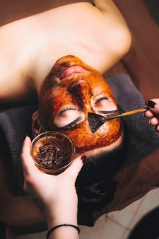 Portrait of a lovely caucasian female leaning on a spa bed having chocolate therapy by applying a chocolate mask on her face in a wellness center.