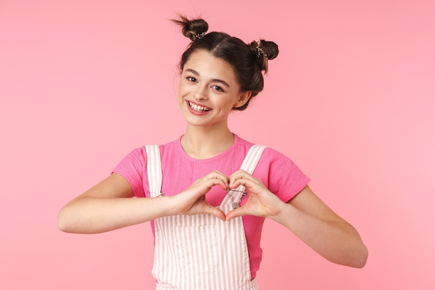 Portrait of lovely charming girl smiling and showing heart with fingers isolated over pink wall