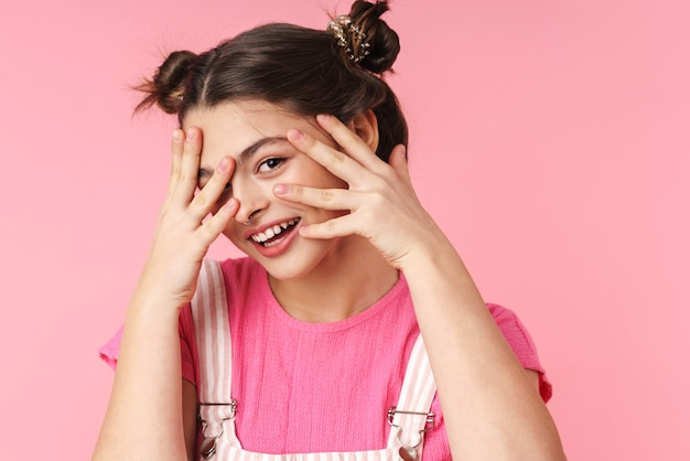 Portrait of lovely charming girl with nose ring posing and smiling at camera isolated over pink wall