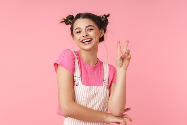 Portrait of lovely charming girl with nose ring showing peace sign and smiling isolated over pink wall