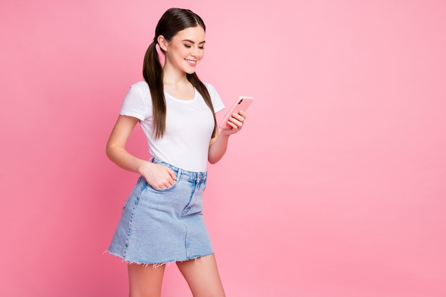Portrait of lovely cheerful focused girl using cell hand pocket