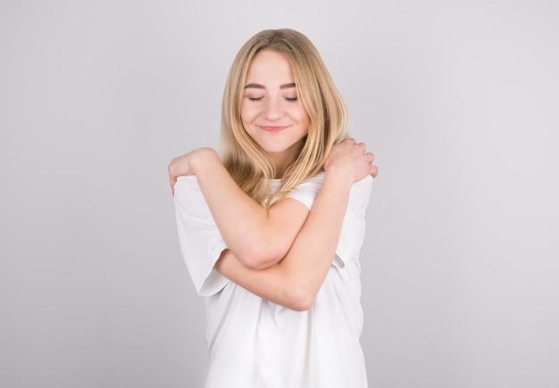 Portrait of lovely cheerful girl hugging herself enjoying herself on grey