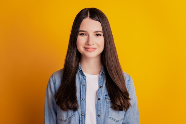 Portrait of lovely cheerful positive girl on yellow background