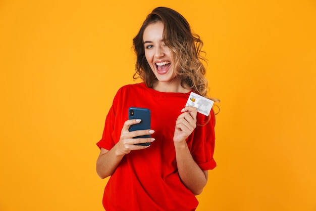 Portrait of a lovely cheerful young woman standing isolated over yellow wall, showing credit card while using mobile phone