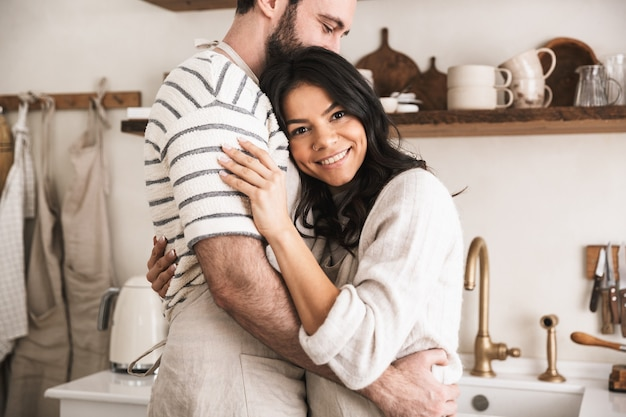 Portrait of lovely couple man and woman 30s wearing aprons hugging together while cooking in kitchen at home