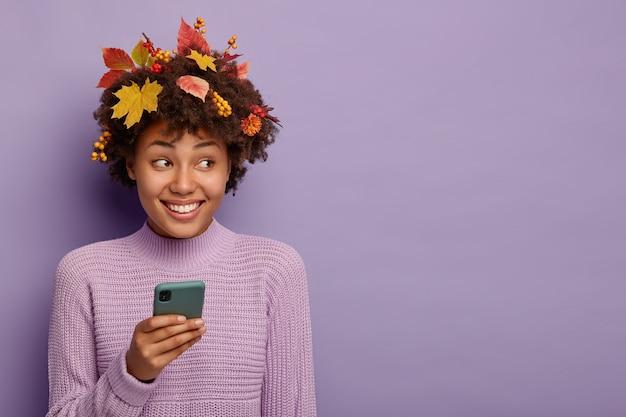 Ritratto di bella donna riccia utilizza lo smartphone, ha foglie di autunno sulla testa, essendo in alto spirito, pone su sfondo viola