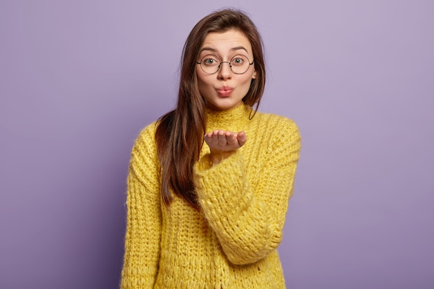 Portrait of lovely dark hared female makes air kiss, sends on distance, expresses love, stretches palm forward, wears glasses winter yellow jumper stands in  over lilac wall body language
