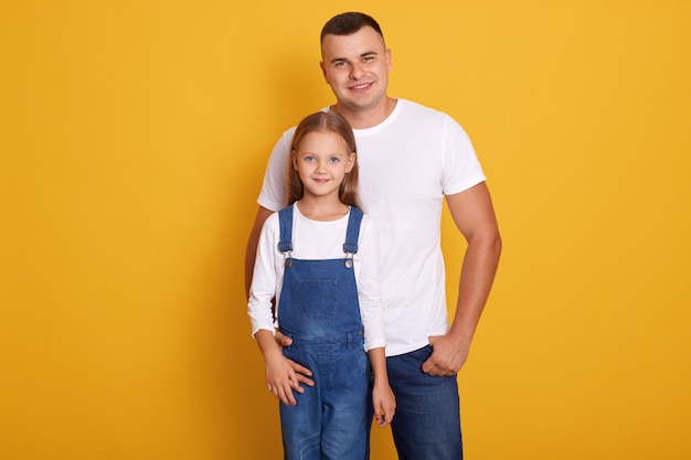 Portrait of lovely daughter smiling and standing with her handsome father isolated over yellow, family wearing casual clothing