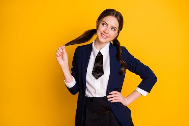 Portrait of lovely dreamy cheerful schoolgirl fantasizing touching ponytail