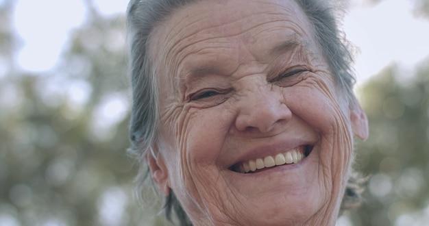 Portrait of lovely elderly woman in the summer park smiling.