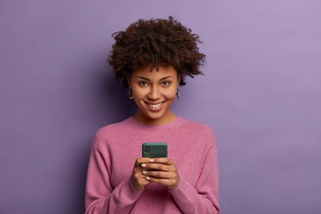 Ritratto di bella donna etnica tiene il telefono cellulare moderno, utilizza il dispositivo elettronico sulla navigazione web, guarda positivamente, connesso a internet wireless, indossa un maglione casual, posa al coperto