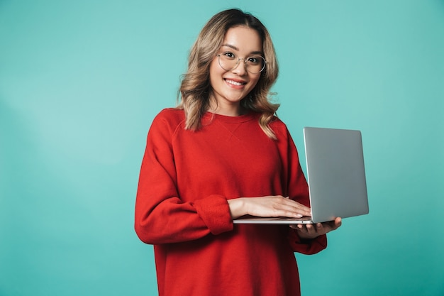 Portrait of a lovely excited young asian woman standing isolated over blue wall, using laptop computer