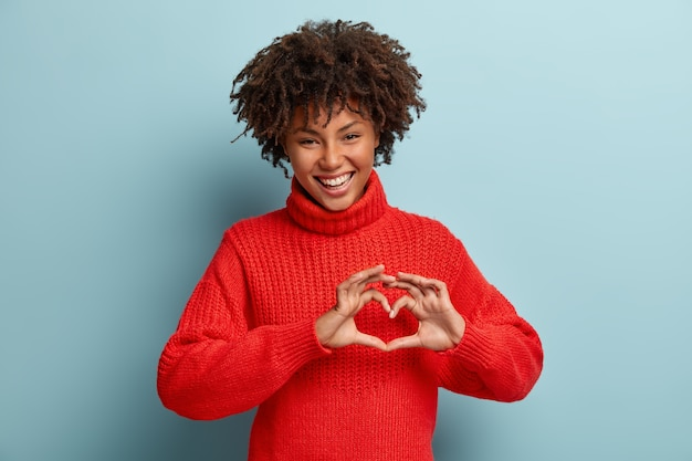 Portrait of lovely female model makes heart gesture, says be my valentine, demonstrates love sign