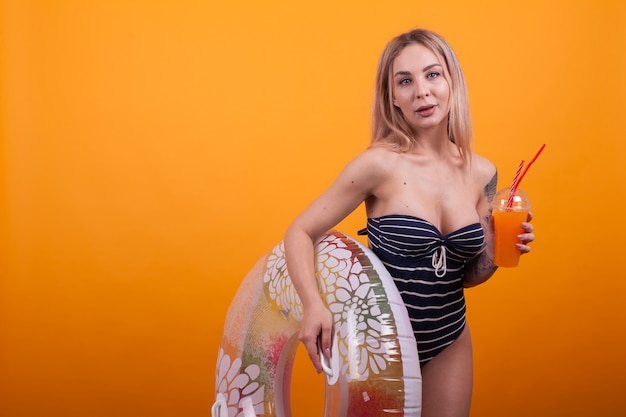Portrait of lovely girl dressed in swimming suit with alcohol cocktail in her hand looking at the camera in studio over yellow background. charming young woman in blue swimming suit with stripes.