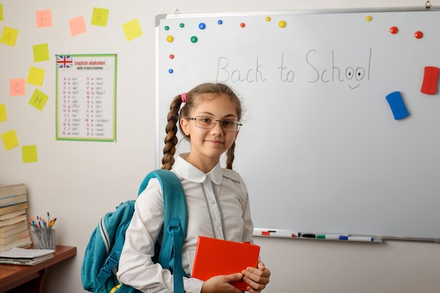 Portrait of lovely girl in glasses standing in classroom with backpack and books