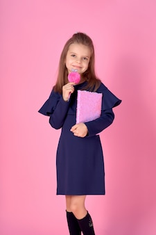 Portrait of lovely girl with notebook and lollipop