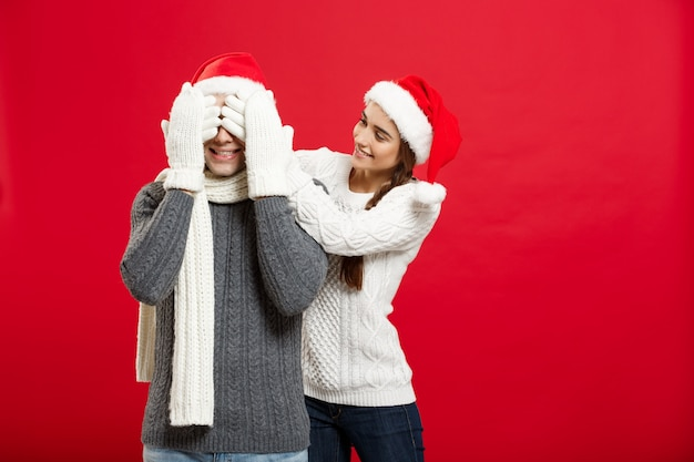 肖像画美しいガールフレンドクリスマスの日に彼女のボーイフレンドの目を閉じます。
