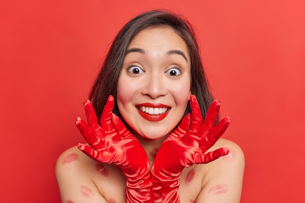Portrait of lovely happy suprised asian woman with dark hair wears gloves keeps hands near face wears minimal makeup stands bare shoulders indoor has kiss traces on body isolated over red wall