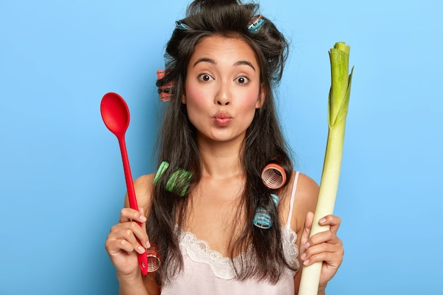 Portrait of lovely housewife keeps lips rounded, wants to kiss husband, holds spoon and green fresh vegetable