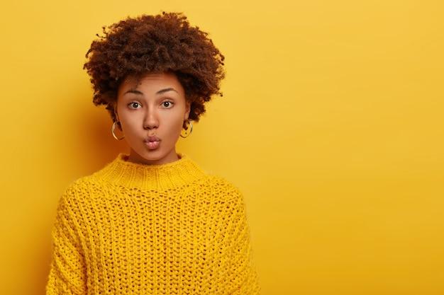Ritratto di bella signora con acconciatura afro, mantiene le labbra piegate, indossa orecchini d'argento e maglione giallo lavorato a maglia ha lo sguardo diretto verso la telecamera si trova al coperto contro lo spazio della copia sfondo luminoso