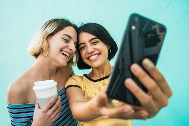 Portrait of lovely lesbian couple having fun and taking a selfie with mobile phone against light blue space. lgbt concept.