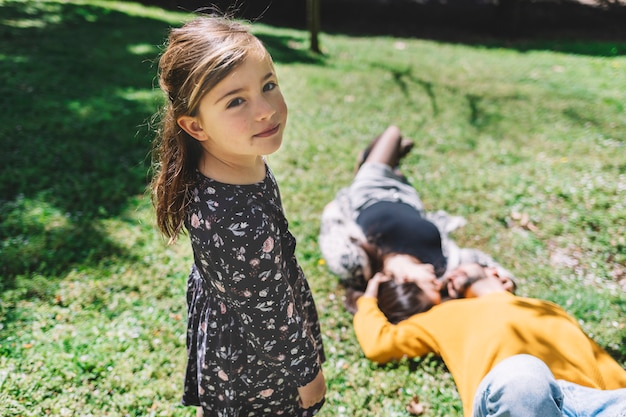 Portrait of a lovely little girl looking camera while her parents laying on ground in a sunny day at park