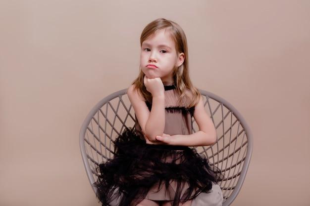 Ritratto di bella bambina seduta con gravi emozioni sulla parete isolata in bel vestito