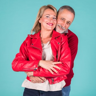 Portrait of lovely mature couple looking at camera against turquoise background